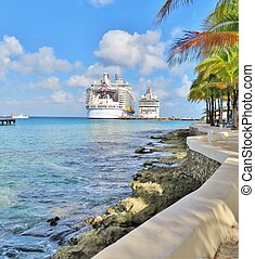 Cruise ships docked at a tropical island