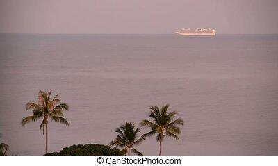 Cruise Summer vacation concept. Cruise ship far away in the sea near the tropical island at sunrise