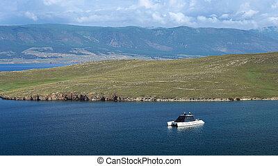 Cruise yacht on the lake near peninsula. Europe