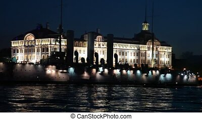 Cruiser Aurora on Neva River night lit by lights at pier