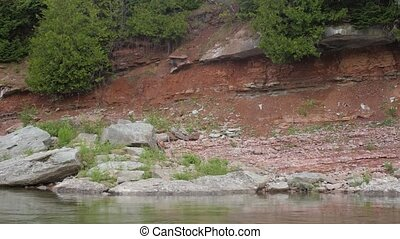 Pan shot of waterfront with pebbles and rocks in the region of Chaleur Bay in Gaspesie in Canada near sea for halt as coast