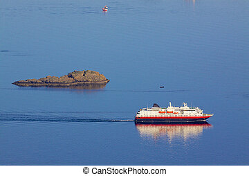 Cruising ship by rock island - Large passenger ship sailing...