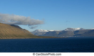 cruising through arctic ford in svalbard, longyearbyen in background