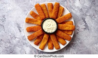 Crumbed fish sticks served with garlic dip sauce on a white...