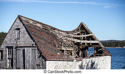 crumbing fishing shack - Sagging roof of an old barn on the...