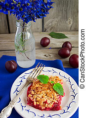 Crumble with plums on a dark blue tablecloths and bouquet of blue flowers