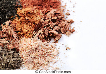 crumbled eyeshadows of different colors on a white background