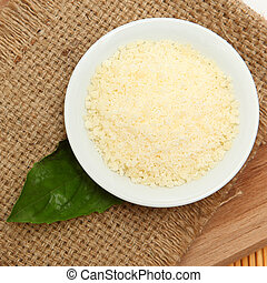 Crumbled Parmesan Cheese in bowl on table.