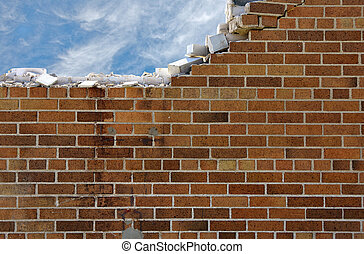 Crumbling brick wall with wispy clouds in blue sky.