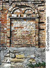 Crumbling brick wall with arch