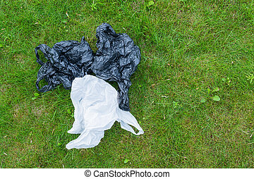 Crumpled cellophane bags on a background of green grass.