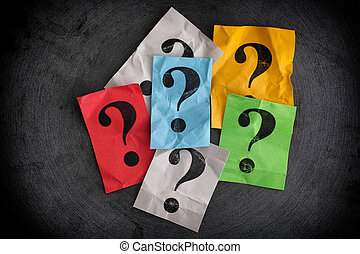 Crumpled colorful paper notes with question marks
