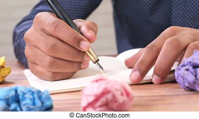 crumpled paper ball and notepad on wooden table