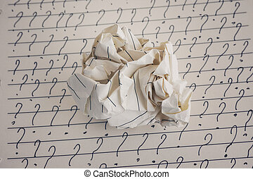 Crumpled paper ball and question marks on sheet of lined paper