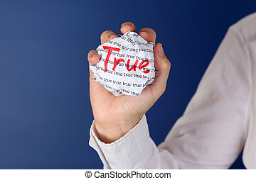 "True - Crumpled paper ball with word ""True"" in woman hand."
