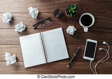 Crumpled paper balls with cup of coffee and notebook on wooden desk