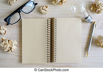 Crumpled paper balls with eye glasses and blank notebook