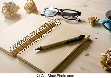 Crumpled paper balls with eye glasses, pen and notebook