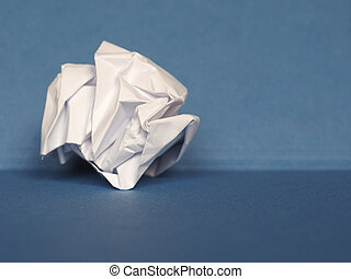 crumpled paper over blue background with copy space