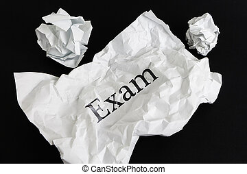 Crumpled paper sheet with word Exam isolated on black