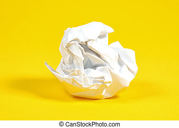 Crumpled Paper Ball on a Yellow Background