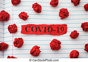 Crumpled piece of red paper with the word COVID-19