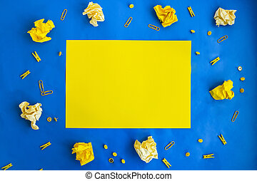 crumpled yellow papers and office supplies in yellow on blue background with paper for your text, frame copy space