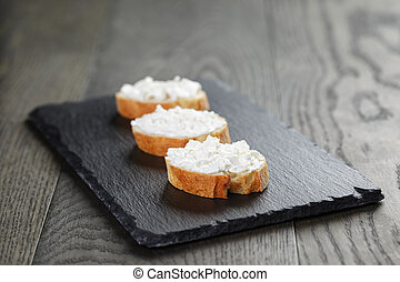 crunchy baguette slices with cream cheese on slate board