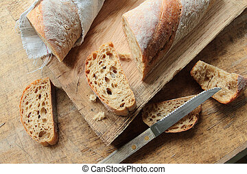 Crunchy bread on a wooden cutting board with knife