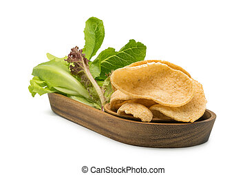 Crunchy prawn cracker and vegetables in a wooden tray
