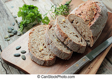 Crunchy wholemeal bread with knife on wooden cutting board