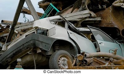 Crushed car on salvage yard lying in a pile of scrap metal....