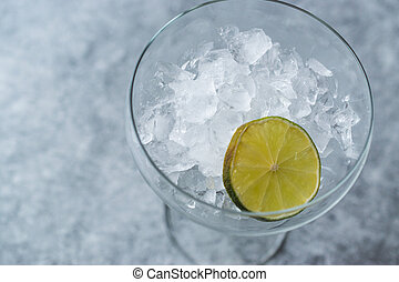 Crushed Ice in Cocktail Glass with Lime on Blue Surface.