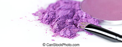 crushed purple eye shadow and makeup brush isolated on white background