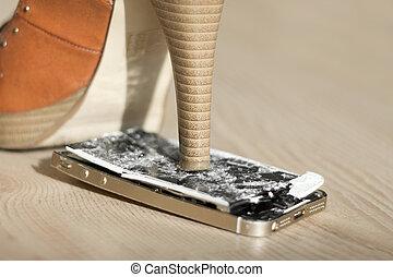 High heel shoe crushing a mobile phone.
