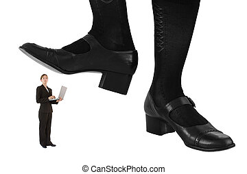 Giant feet preparing to crush a female business professional wearing tailored suit and holding a laptop computer. Conceptual image isolated on a white background.