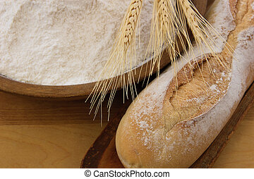 Crusty baguette bread with wooden bowl full of flour -...