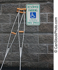 crutches against a brick wall in a handicapped parking stall