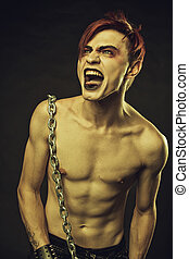 Cry - Redhead chained young man screaming over dark...