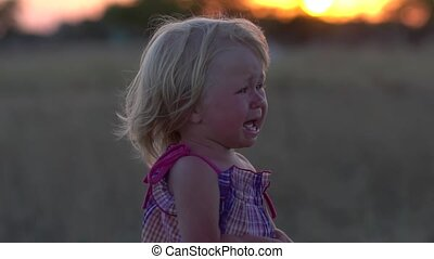 Crying baby. Child at sunset in the meadow. Children's crying.