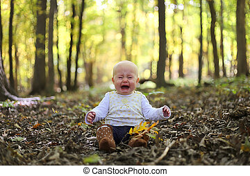 Crying Baby Girl in Autumn Woods under Yellow Maple Trees