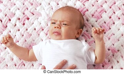 crying baby girl lying on knitted plush blanket - babyhood,...