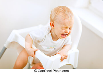 Crying baby in baby chair