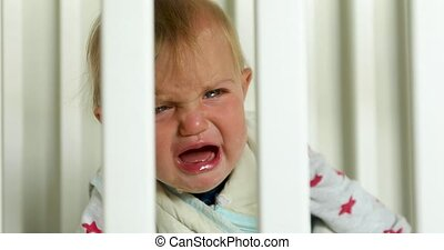 Crying baby in crib at home - Crying baby girl in crib at...