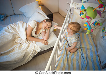 Crying baby waking up and reaching his mother at night -...