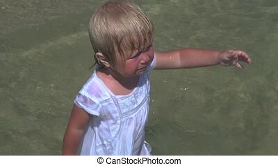 Crying baby with open arms standing in water. - Disobedient ...