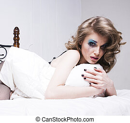 crying blonde woman laying in bed depressed