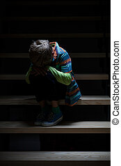 Crying boy sitting on staircase - View of crying boy sitting...