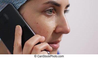 crying doctor or nurse calling on smartphone - medicine, ...