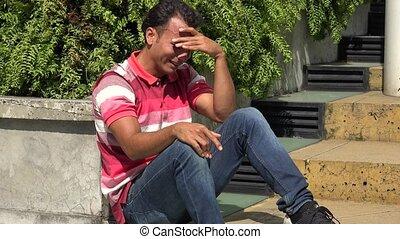 Crying Hispanic Male Sitting